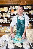 Salesman standing at counter wrapping wedge of cheese in cheese shop