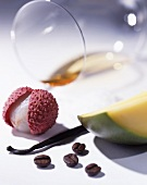 White wine, a lychee, a vanilla pod, coffee beans and a portion of mango
