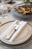Stylish place setting with a wooden plate, napkin and silver cutlery