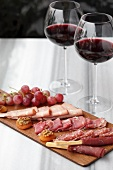 A selection of cold meats with grapes and two glasses of red wine