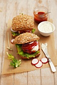 Hamburgers with tartare sauce, ketchup and radishes
