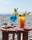 Cocktails and appetisers on a small wooden table at the beach