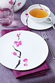 A place setting for afternoon tea, decorated with a flower motif