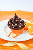 A chocolate cupcake with sugar confetti and oranges