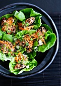 Lettuce leaves filled with chicken, carrots and sesame seeds (Asia)