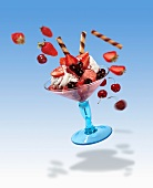 A flying strawberry sundae with flying ingredients