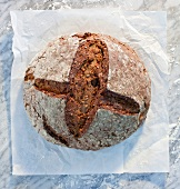 A rustic loaf of bread on paper, on a marble slab, dusted with flour