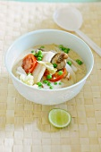 Coconut soup with fish, peas and tomatoes