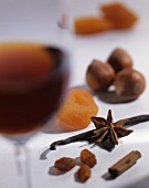 A glass of dessert wine, spices, nuts and dried fruits