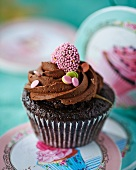 A chocolate cupcake with a decorative heart