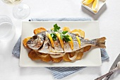 Grilled gilt-head bream with oranges on top of potato slices