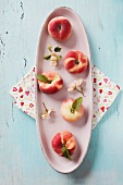 Peaches on a ceramic dish with blossom