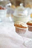 Muffins topped with buttercream on a torte stand