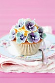 A cupcake decorated with blue flowers