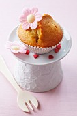 A muffin decorated with a flower made from edible paper