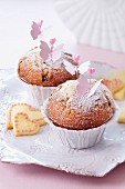 Muffins with icing sugar and decorative butterflies on spikes
