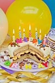 Sponge layer cake with candles for a birthday, and balloons
