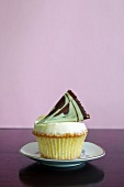 A cupcake topped with a fan of chocolate and pistachio