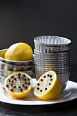 Lemons with cloves and muffin tins on a white plate