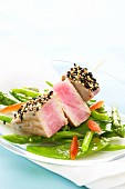 Tuna skewer on a bed of steamed vegetables