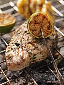 Barbecued tuna steak with limes on the barbecue