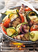 Assorted barbecued vegetables in a tray on the barbecue