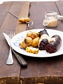 Barbecued bloodwurst with new potatoes, corn and mustard sauce