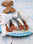 Sardines with tomatoes, onions and garlic cooked in parchment paper