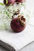 Mangosteen on a linen tablecloth with white flowers in the background