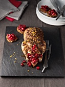 A small, stuffed duck with cranberries and oranges