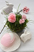 An idea for an Easter decoration: a porcelain hare, and paper pinks in a nest made of moss