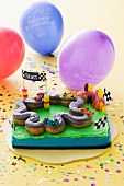 A child's birthday cake (a racing track) and balloons