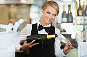 A waitress pouring sparkling wine in a restaurant