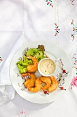 Breaded prawns on small skewers with a dip and salad