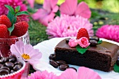 Chocolate cake on a dessert plate among pink floral decorations