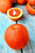 A blood orange with blood orange halves in the background