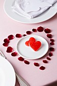 Rose petals arranged in shape of heart surrounding sweets on plate