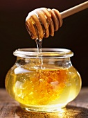 Honey dripping from a honey spoon into a jar