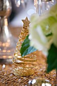 A golden glittering Christmas tree as table decoration