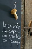 Handwritten menu and fresh penny bun mushroom hanging against blackboard in kitchen