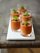 Several glasses of gazpacho with basil