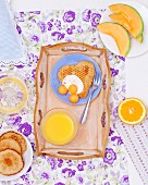 A breakfast tray with a heart-shaped pancake with yoghurt and melon balls and a glass of orange juice