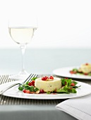 Individual Stilton tart with pomegranate seeds and rocket