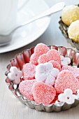 Small cake mould used as dish for sweets & flower-shaped sugar cubes