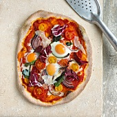 A pizza with quail's eggs, red onions, parmesan and radicchio