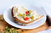 Black bread topped with tofu and pumpkin seed spread
