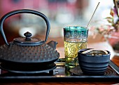 A tea-themed still life featuring a black teapot