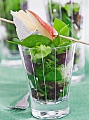 Salad leaves in a glass with a pear and cheese skewer