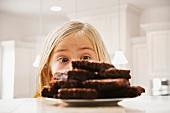 Girl (6-7) looking at heap of brownies