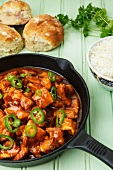 Spicy turkey goulash in a pan, with rice and bread rolls
